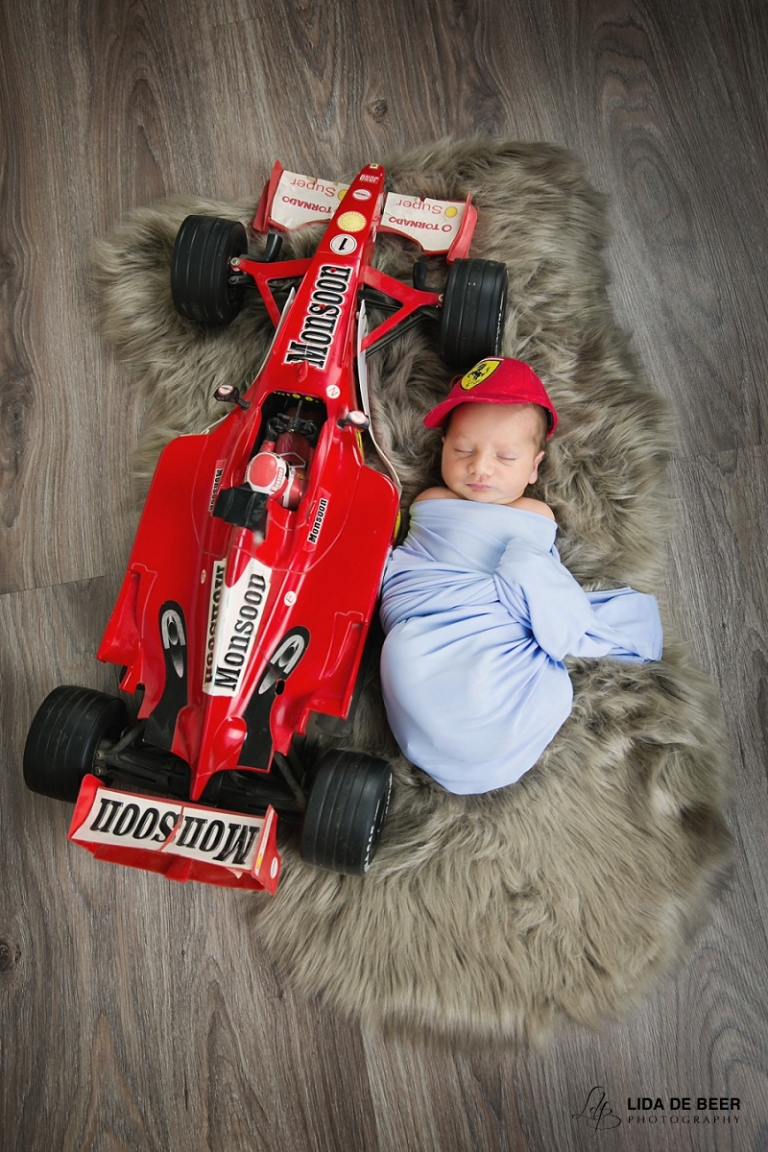 newborn boy with red ferrari