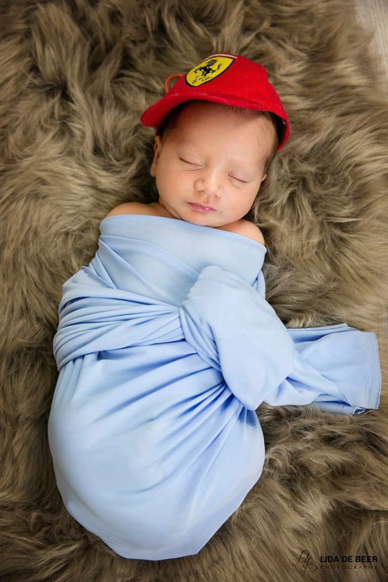Newborn boy with Ferrari cap